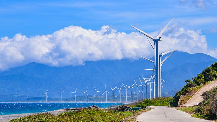 A wind farm along a shoreline in the Philippines, with mountains in the background.