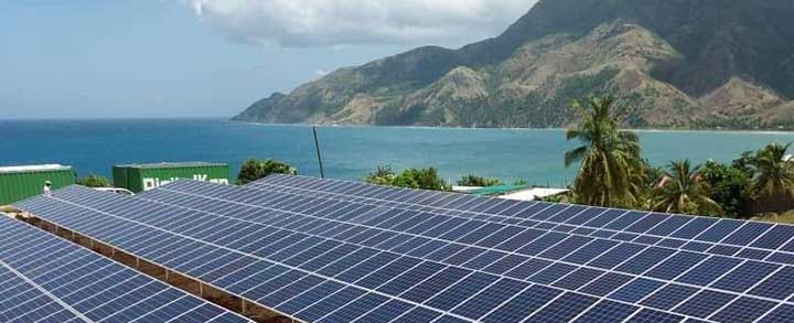 A mini-grid in Tiburon, Haiti, with the sea and mountains in the background.