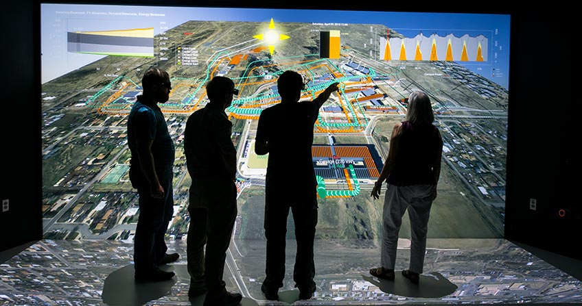 Photo of four researchers looking at wall of 3-D data.