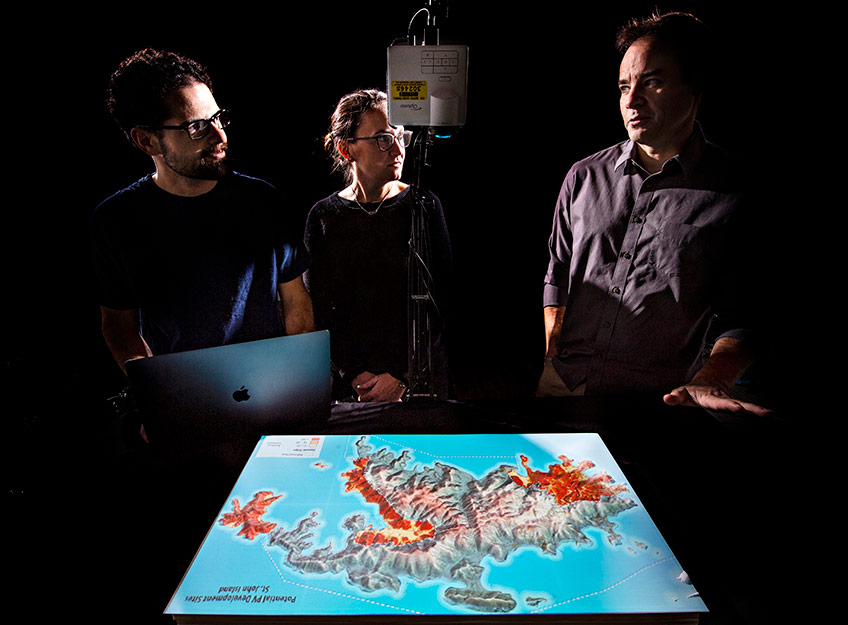 Photo of three researchers examining a 3-D visualization of data on a model of an island.