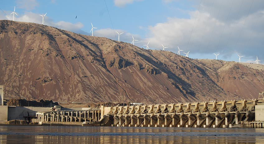 Photo of wind turbines on a hill above a hydropower dam.