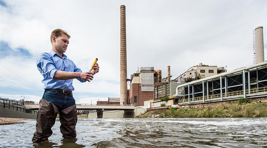 Photo of a man standing in water looking at a water sample in front of a hydropower plant.