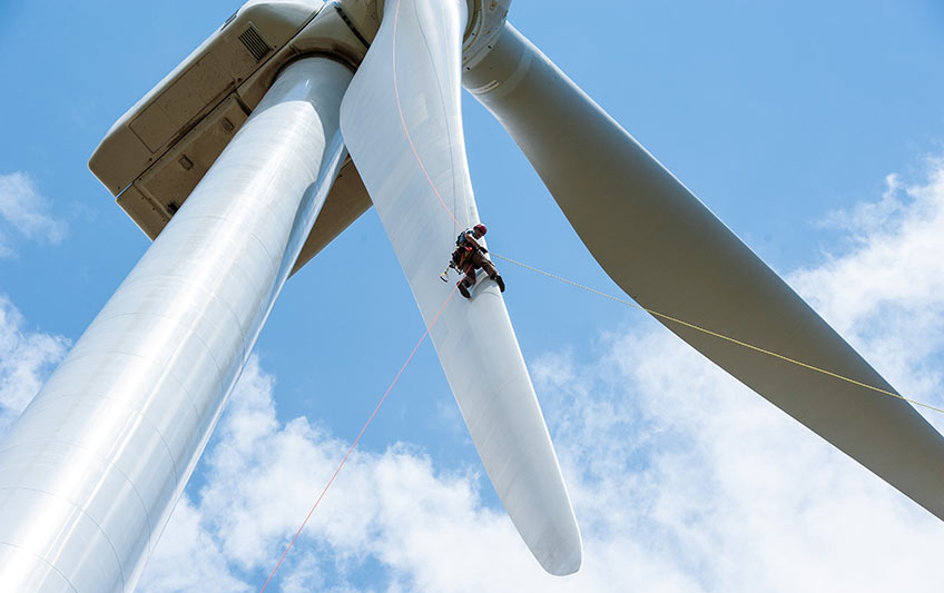 A man rappels down the leading edge of a wind turbine blade.