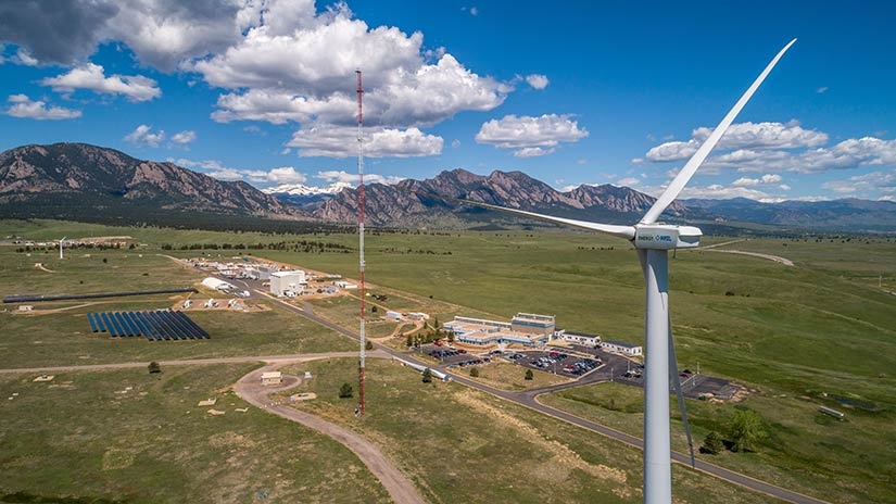 A wind turbine stands in the foreground with roads and buildings below. A mountain range spans the background.