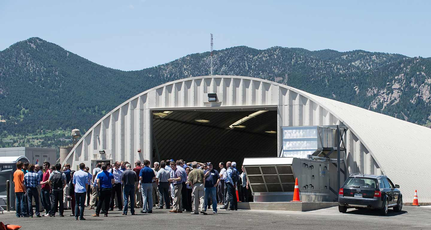 A large group of people stand outside of a white, half-cylindrical facility with mountains in the background.