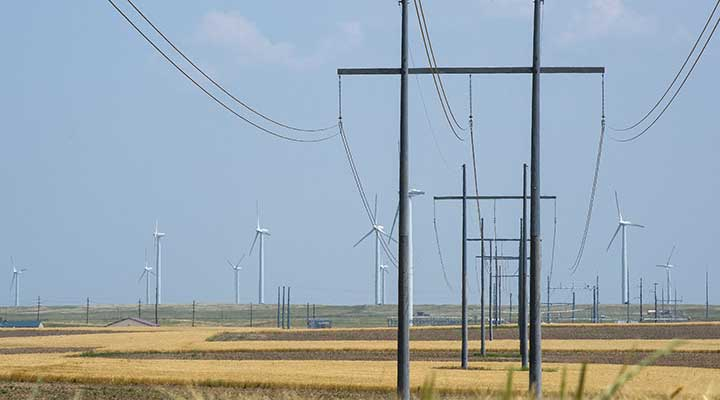 A photo of a transmission power line in a brown field with wind turbines in the background.