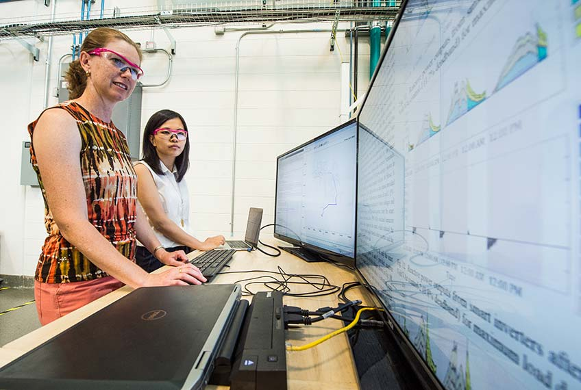 Two NREL partners in their lab at the Energy Systems Integration Facility.
