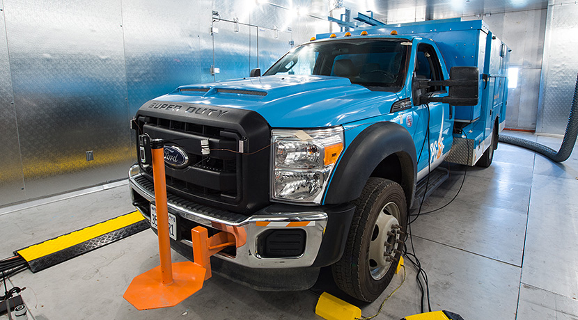 Photo of blue Ford utility vehicle in an environmental chamber, with shiny silver walls, for thermal testing.