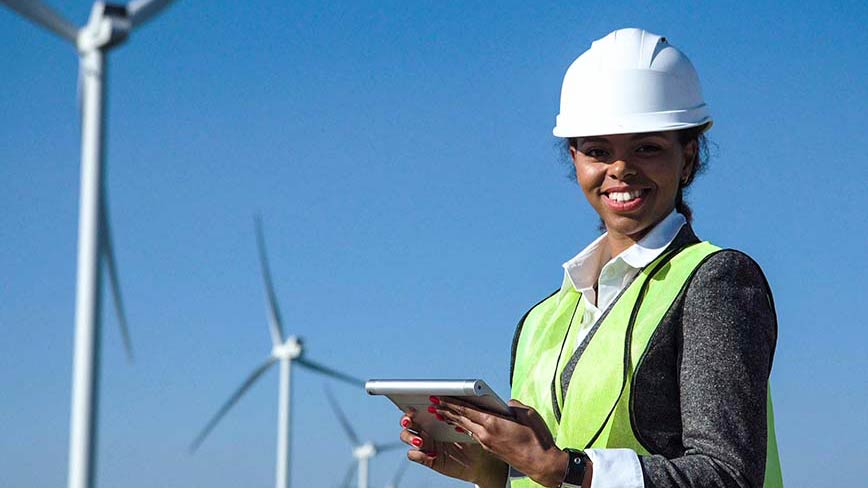 A woman wearing a hardhat with wind turbines in the background