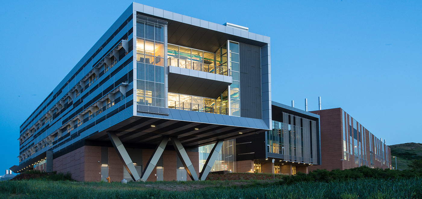 An evening photograph of the Energy Systems Integration Facility on NREL's campus.